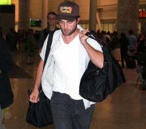 Rob Pattinson not over-doing it with the baseball cap + white v-neck tee.